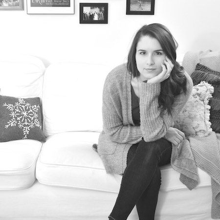 Sarah E. K. Lentz sitting on white couch, legs crossed, head resting on right hand with right elbow on right knee, looking into camera