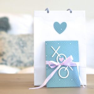 White gift bag with blue heart. Blue card propped up in front with XOXO on front.