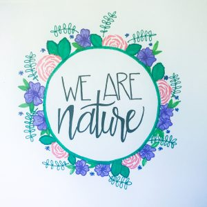 """We Are Nature"" handwritten inside drawn floral wreath"