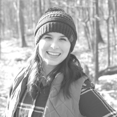 Sarah E. K. Lentz in forest wearing toque and smiling at the camera